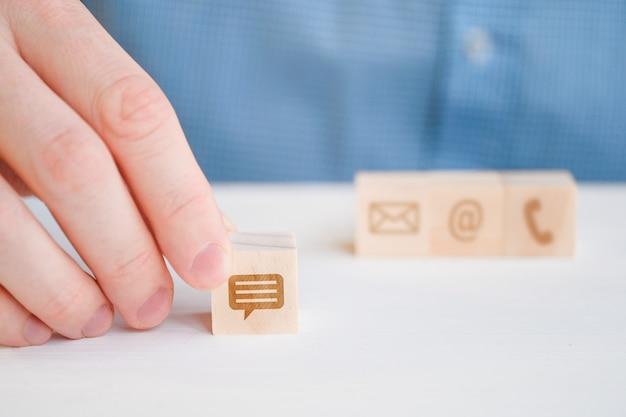 Un uomo in una camicia tiene con la mano un'icona astratta su un cubo di messaggio in legno