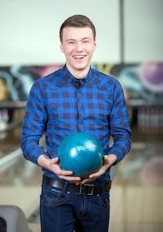 Un uomo in una camicia tiene una palla da bowling.