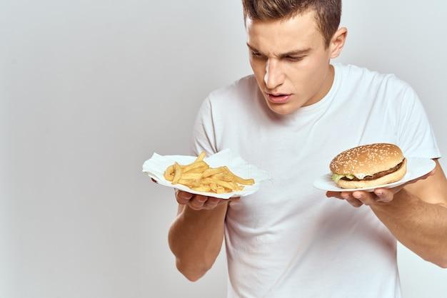 Un uomo in una maglietta bianca con hamburger di fast food nelle sue mani