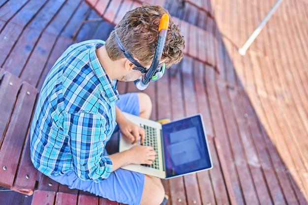 Un uomo in una maschera subacquea, in vacanza al mare, lavorando a un computer.
