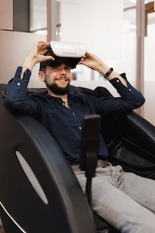 Un uomo in una poltrona massaggiante con tecnologia vr