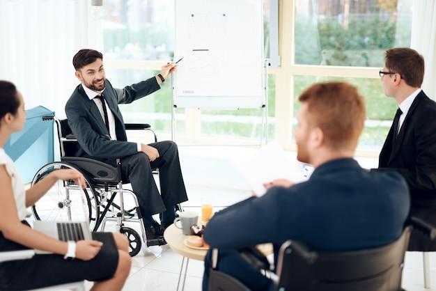Un uomo in una sedia a rotelle sta puntando al grafico sulla lavagna.