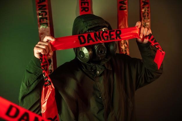 Un uomo in una tuta protettiva scura con una maschera antigas sul viso e un cappuccio in testa in posa in piedi vicino a una parete verde con nastri di pericolo sul viso. concetto di pericolo