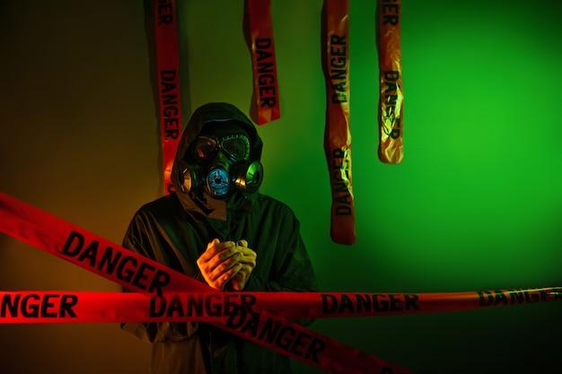 Un uomo in una tuta protettiva verde scuro con una maschera antigas sul viso e un cappuccio in testa in posa in piedi vicino a una parete verde con nastri di pericolo appesi. concetto di pericolo