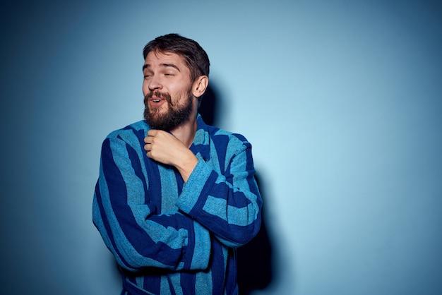 Un uomo in una veste blu su un gesto leggero con le sue mani modella abiti da casa.