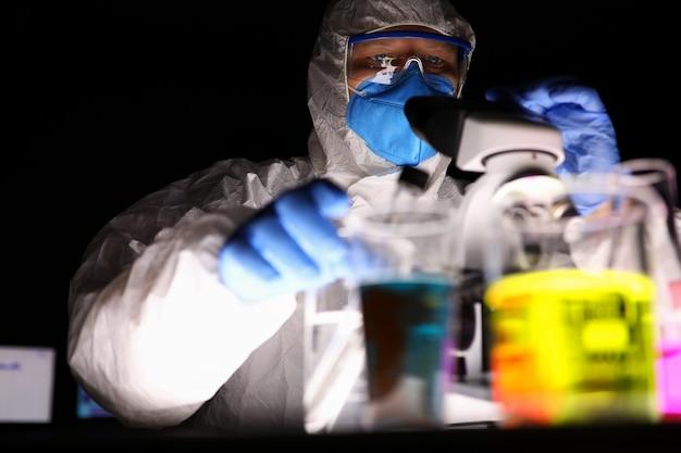 Un uomo in uniforme protettiva e maschera guarda attraverso un microscopio