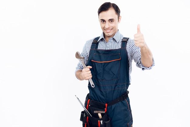 Un uomo in uniforme tiene una chiave regolabile.