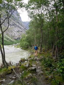Un uomo indefinito con attrezzatura turistica sta camminando sopra le pietre in una foresta in norvegia.