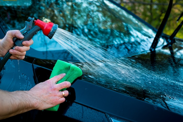 Un uomo lava un cofano dell'auto usando una spugna e un tubo flessibile con acqua nebulizzata, pulizia dell'auto.