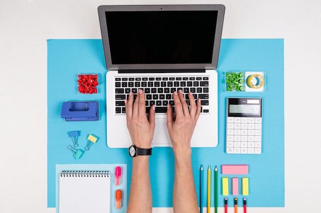 Un uomo lavora con il computer portatile isolato su bianco e blu
