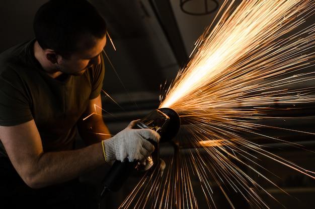 Un uomo lavora con il metallo e le scintille volano magnificamente