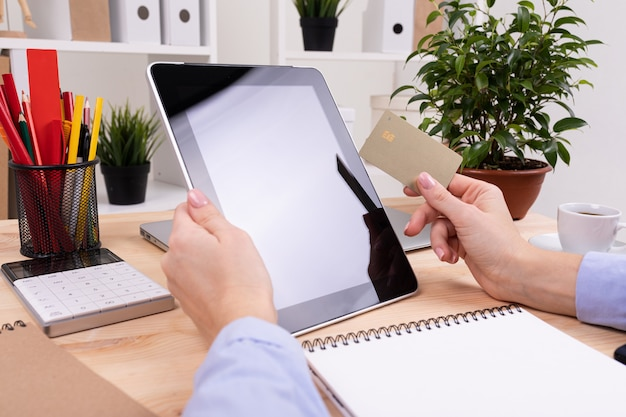 Un uomo lavora con un tablet e fa appunti sul suo desktop con calcolatrice, penne, matite, carta, telefono e una pianta in ufficio