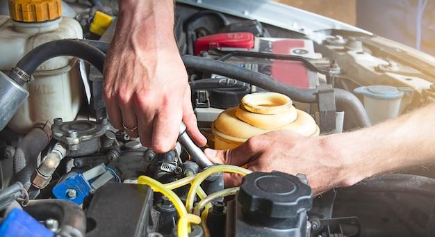 Un uomo lavora in un garage. un uomo esegue la riparazione e la manutenzione dell'auto.