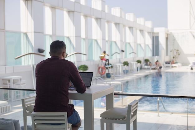 Un uomo lavora su un laptop vicino alla piscina. libero professionista. concetto di lavoro di vacanza