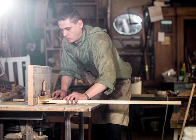 Un uomo lavora sulla macchina con il prodotto in legno