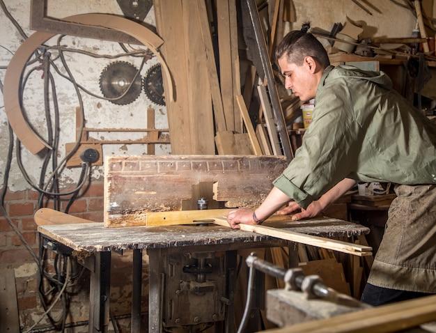 Un uomo lavora sulla macchina con la produzione di prodotti in legno