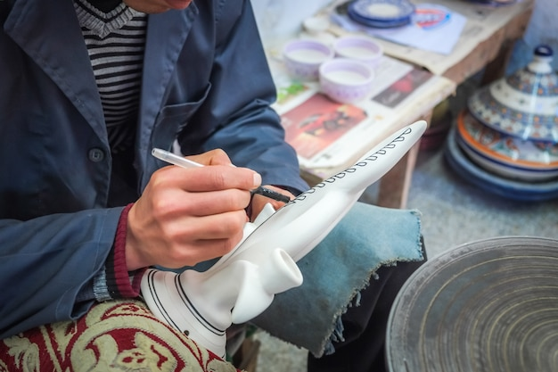 Un uomo marocchino dipinge su una ceramica ceramica. medina di fez, marocco.