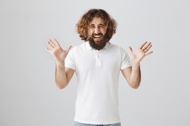 Un uomo mediorientale con la barba urla e stringe la mano sopraffatto