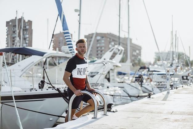 Un uomo nel porto che prepara lo yacht per il viaggio