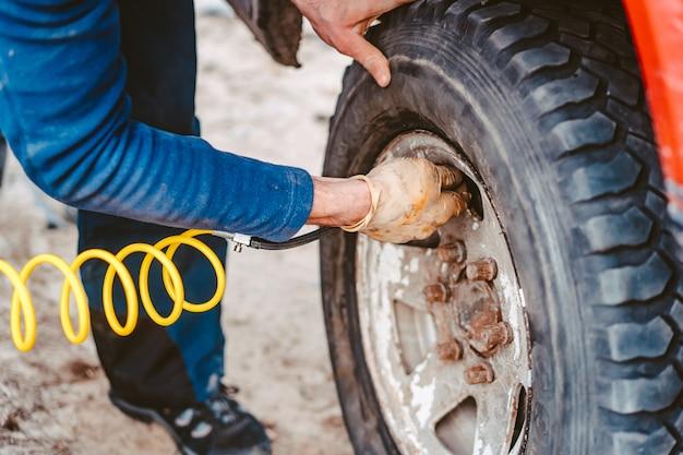 Un uomo pompa la ruota pneumatica con un compressore