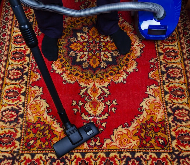 Un uomo pulisce un vecchio tappeto con un aspirapolvere elettrico