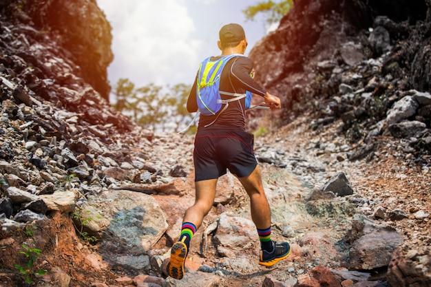 Un uomo runner di trail e i piedi dell'atleta che indossano scarpe sportive per il trail running nella foresta