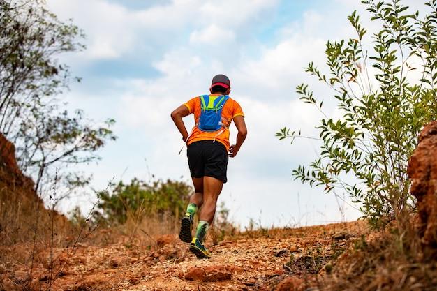 Un uomo runner of trail. e i piedi dell'atleta che indossano scarpe sportive per il trail running in montagna