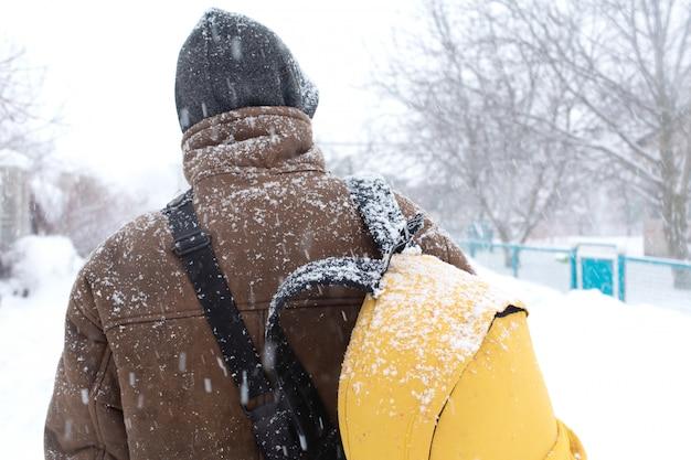 Un uomo rustico cammina per strada in inverno con uno zaino giallo. bufera di neve