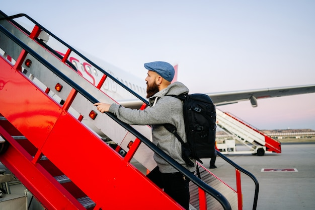 Un uomo sale sull'aereo dalla passerella giù per le scale