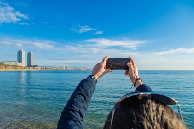 Un uomo scatta una foto al telefono della passeggiata nella città di barcellona. messa a fuoco selettiva.