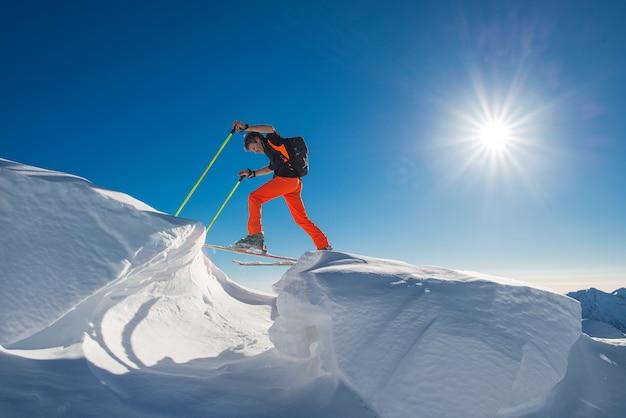 Un uomo sciatore alpino arrampica su sci e pelli di foca in così tanta neve con ostacoli