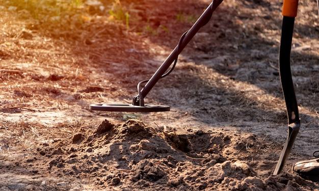 Un uomo scruta un buco scavato nella foresta con un metal detector e una pala in mano