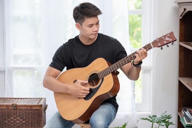 Un uomo seduto e suonare la chitarra su una sedia.
