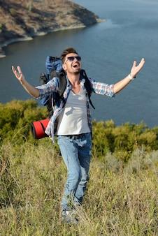 Un uomo si erge su una montagna e alza le mani.