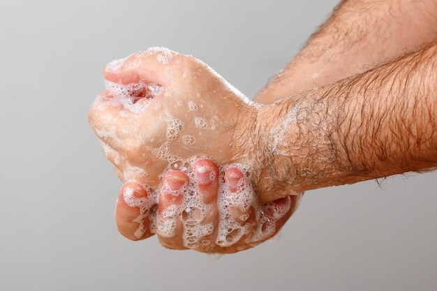 Un uomo si lava le mani su sfondo bianco