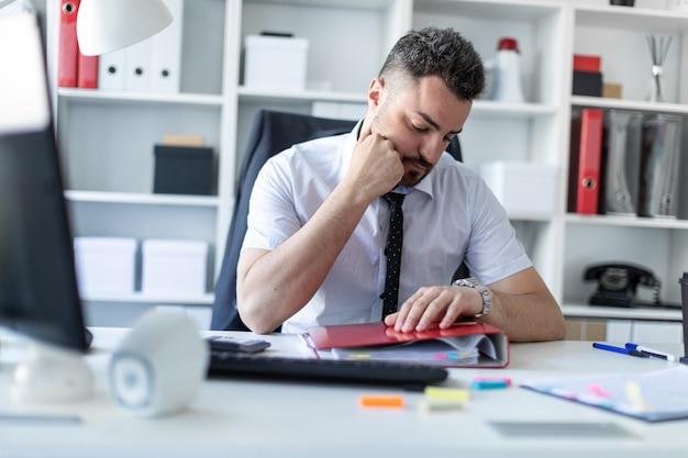 Un uomo si siede a un tavolo in ufficio e guarda l'orologio da polso.