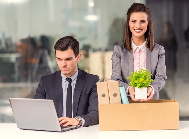 Un uomo si siede al computer mentre la ragazza raccoglie cose.