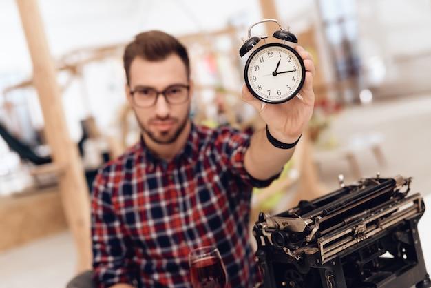 Un uomo si siede e mostra un orologio alla telecamera.