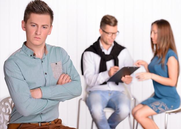 Un uomo si siede ferito mentre sua moglie parla con uno psicologo.