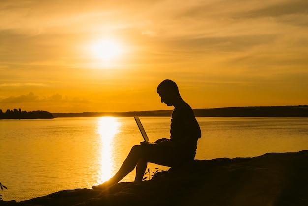 Un uomo si siede sulla riva del fiume con un computer portatile in mano al tramonto.