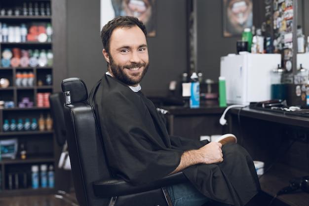 Un uomo si siede sulla sedia da barbiere nel negozio di barbiere