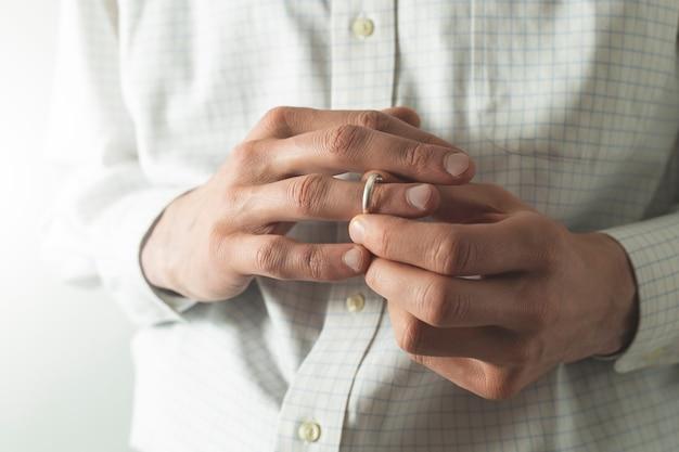 Un uomo si toglie una fede dal dito. il marito tradisce sua moglie. il concetto di tradimento.
