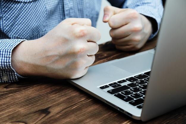 Un uomo siede in una camicia a un laptop stringendo i pugni. stress e fallimento.
