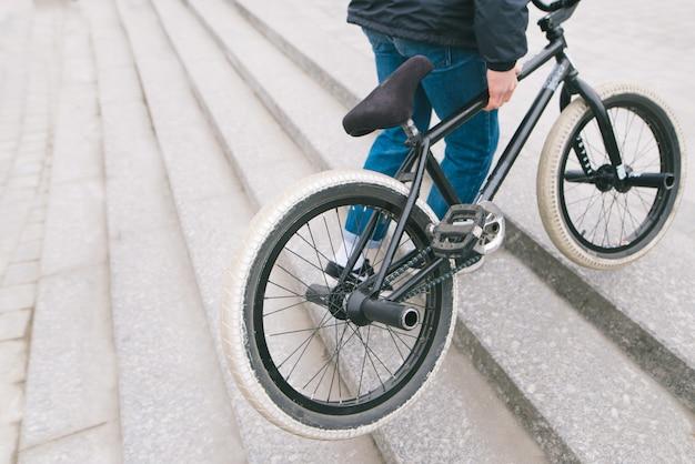 Un uomo solleva la bici bmx sulle scale verso l'alto. un uomo con una bici bmx. copyspace.