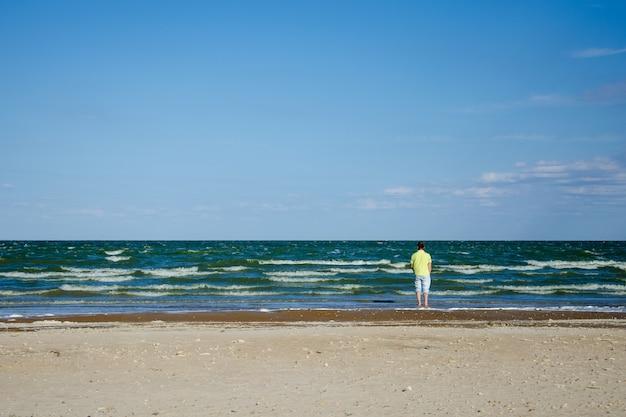 Un uomo solo e triste si trova con le spalle al mare e guarda in lontananza. solo su una spiaggia deserta ammirando le onde. concetto di cattivo umore, depressione, rottura delle relazioni amorose. copia spazio