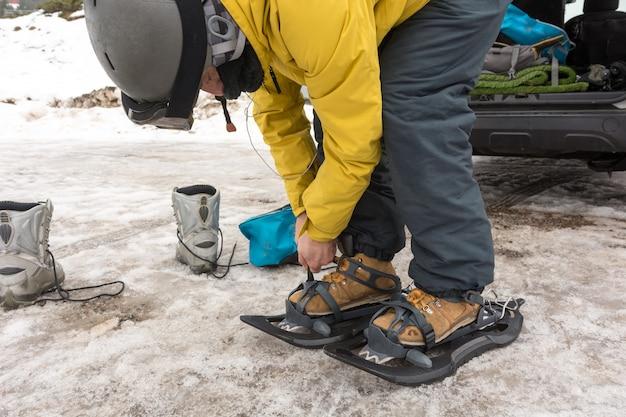 Un uomo sportivo che indossa le racchette da neve per iniziare un'escursione in montagna innevata.