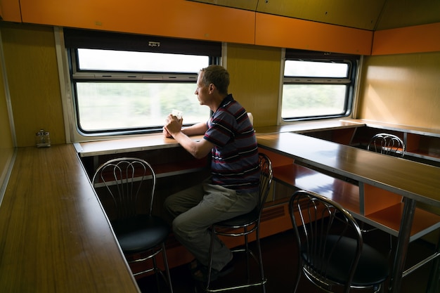 Un uomo sta cavalcando un vagone ristorante in treno.