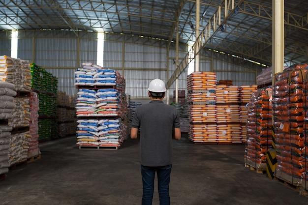 Un uomo sta controllando la qualità del prodotto nel magazzino. magazzinaggio, controllo qualità