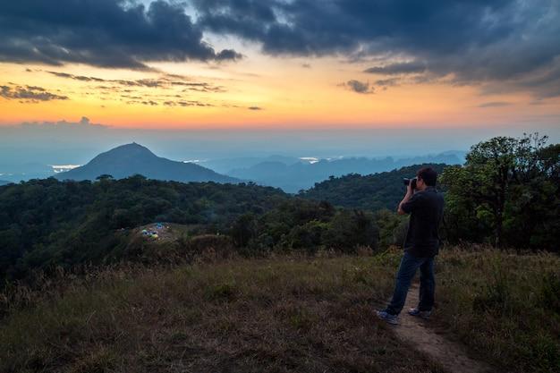Un uomo sta in cima alla montagna