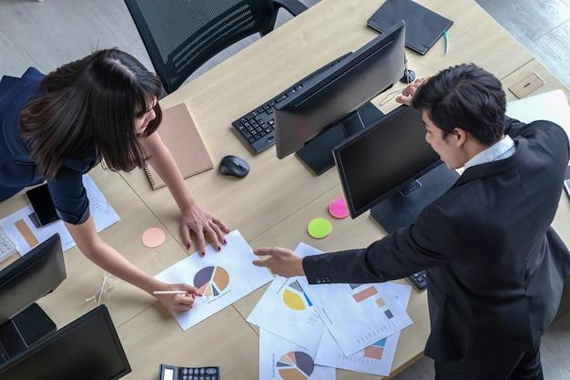 Un uomo sta spiegando il lavoro a una ragazza alla scrivania.
